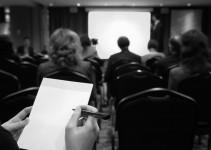 Business seminar. Notebook in women's hands against the background of the business room.